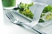 stock photo of escarole  - closeup of a plate with a green salad and a measuring tape and a green smoothie - JPG