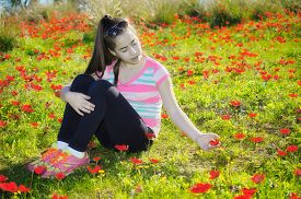 stock photo of windflowers  - Teenage girl with braces on her teeth in a field of wild red anemone coronaria (windflower) flowers blooming in the Galilee Israel after the winter rains ** Note: Soft Focus at 100%, best at smaller sizes - JPG