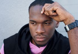 stock photo of swagger  - Close up portrait of a handsome young black man thinking - JPG