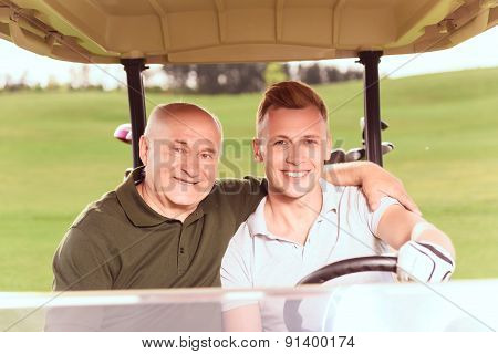 Senior and young men driving in course