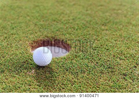 Close up of golf ball near hole