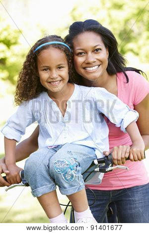 Young African American Mother And Daughter Cycling In Park