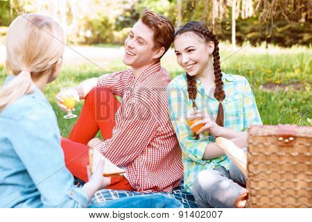 Young people eating and drinking during picnic