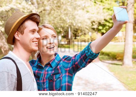 Young couple doing selfie in park.