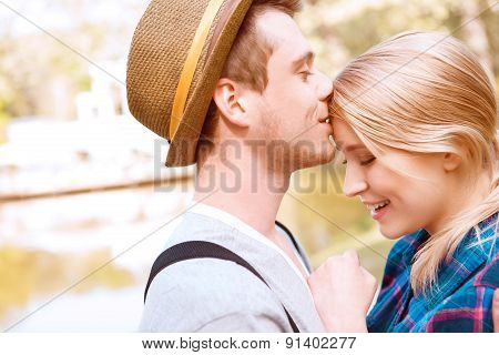 Handsome man kissing his girlfriend on forehead.