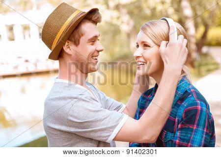 Handsome man putting headphones on pretty girl