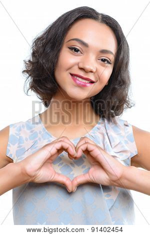 Young mulatto girl showing heart with her fingers