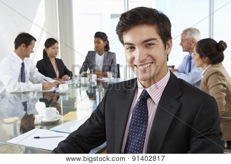 Businessman Sitting Around Boardroom Table With Colleagues