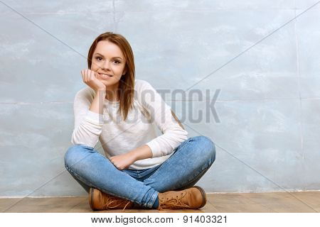 Pleasant woman sitting cross-legged leaning on her head.