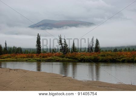 Rain, fog and low clouds on the mountain river.
