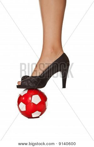 Caucasian blond business woman leg in high heel with soccer ball