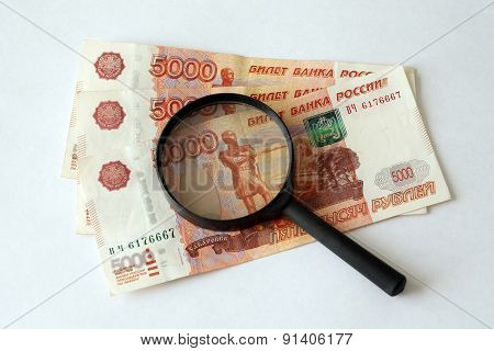 Russian money and magnifying glass