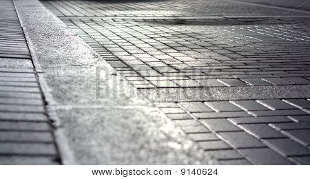 Reflections And Patches Of Light On Asphalt