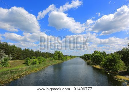 Nice clouds in sky over river at a sunny summer day