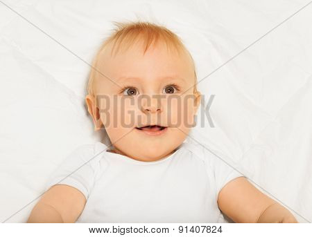 Amazed face of small baby wearing white babygro