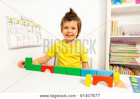 Laughing cute boy putting blocks in sequence