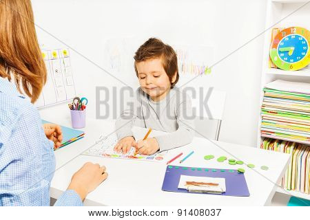 Boy colors shapes during ABA with therapist near