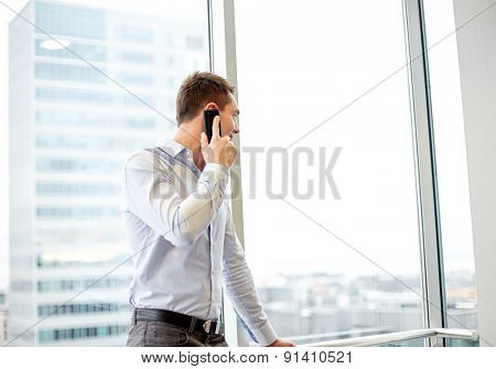 business, technology and people concept - happy businessman calling on smartphone and looking out office window