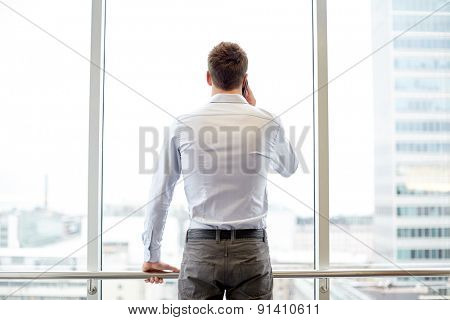 business, technology and people concept - businessman calling on smartphone and looking out office window