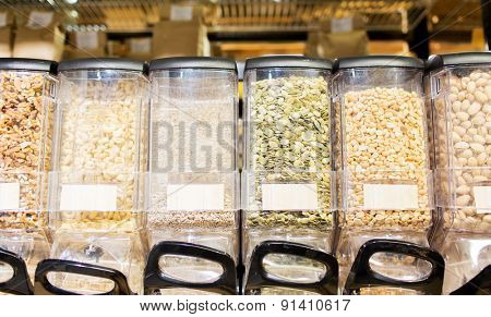 sale and eco food concept - row of jars with nuts and seeds at grocery store