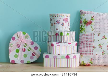 Interior detail. Home shelf with shabby chic gift boxes and pillow on it over blue wall