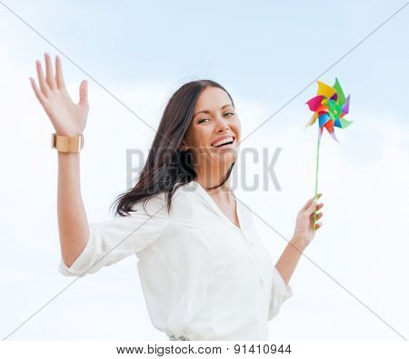 summer holidays, vacation and ecology concept - girl with windmill toy on the beach