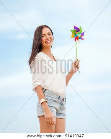 summer holidays, vacation and ecology - girl with windmill toy on the beach