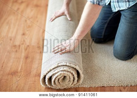 repair, building and home concept - close up of male hands rolling carpet