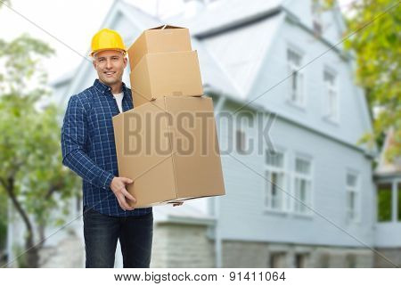 repair, building, construction, loading and delivery concept - smiling man or loader in helmet with cardboard boxes over living house background