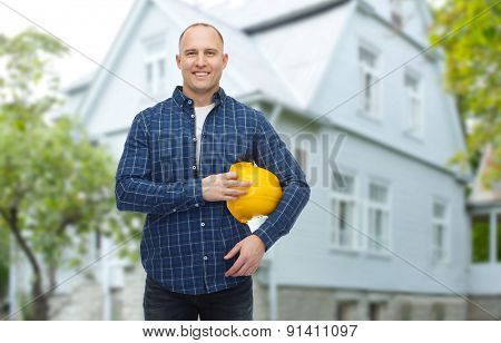 repair, building, construction and maintenance concept - smiling man holding helmet over living house background