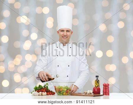 profession, vegetarian, food and people concept - happy male chef cooking vegetable salad over christmas holidays lights background