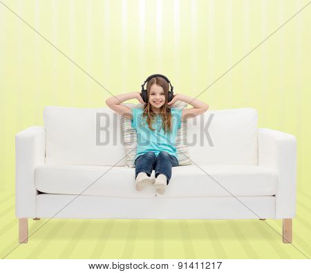 leisure, technology, music and childhood concept - smiling little girl in headphones listening to music sitting on sofa over yellow striped background