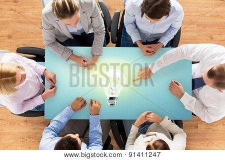business, people and team work concept - close up of creative team sitting at table and pointing finger to lighting bulb in office