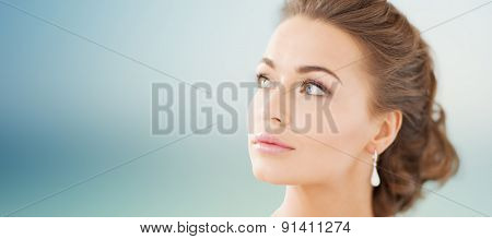 people, beauty, jewelry and accessories concept - beautiful woman with diamond earrings over blue background