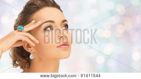 beauty, jewelry, people and accessories concept - close up of woman face with cocktail ring on hand and earrings over blue holidays lights background