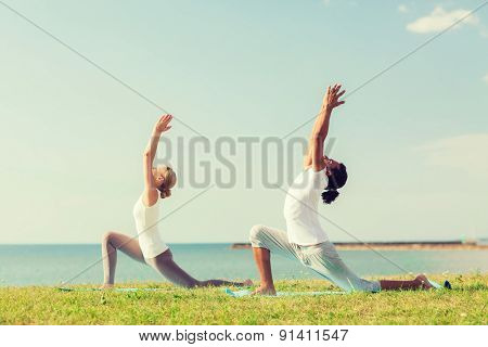 fitness, sport, friendship and lifestyle concept - smiling couple making yoga exercises on mats outdoors