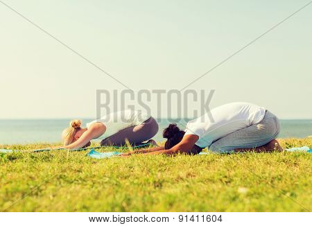 fitness, sport, people and lifestyle concept - couple making yoga exercises on mats outdoors