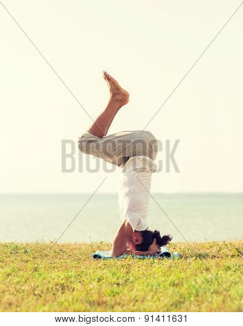 fitness, sport, people and lifestyle concept - man making yoga exercises on sand outdoors