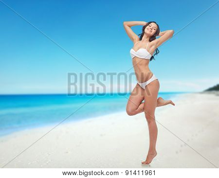 people, swimwear, tourism, travel and summer concept - happy young woman posing in white bikini swimsuit with raised hands and standing on one leg over beach background