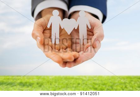 people, homosexuality, same-sex marriage and love concept - close up of male gay couple holding love and gender symbol over blue sky and grass background