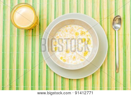 Top view of ready to eat breakfast with bowl of cork flakes and milk, full glass of orange juice on striped yellow green bamboo mat