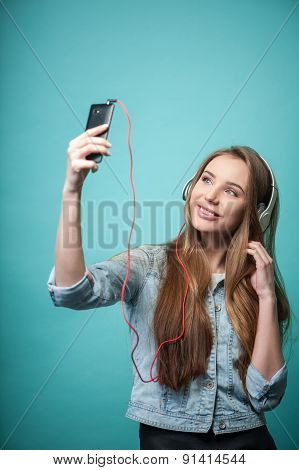 Cheerful Hipster woman with headphones and mobile phone