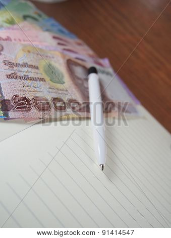 Banknotes Money With Pen On  Opened Notebook