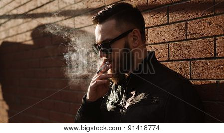 Side view of handsome bearded man smoking a cigarette