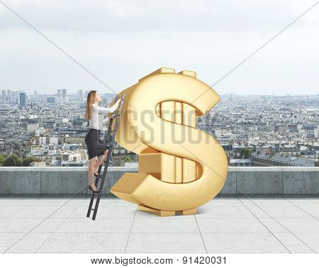 Young Lady Is Climbing On The Huge Golden Dollar Sign On The Rooftop. Paris Panoramic View
