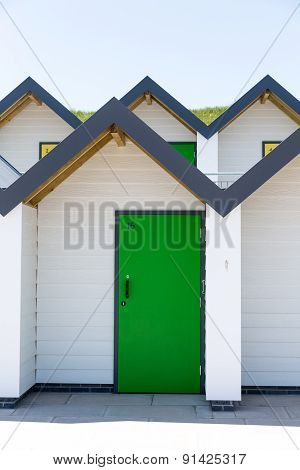 Colourful Green Door, With Each One Being Numbered Individually, Of White Beach Houses On A Sunny Da
