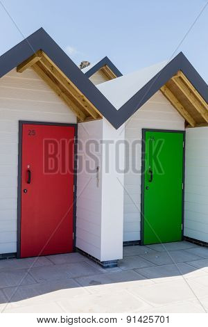Colourful Doors Of Red And Green, With Each One Being Numbered Individually, Of White Beach Houses O