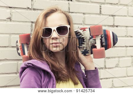 Teenage Girl In Sunglasses Holds Skateboard