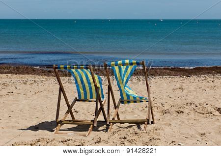 Two Blue And White Striped Beach Chairs On The Sand Beach With Its Back Towards The Camera
