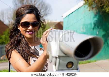 young woman enjoying a view with a telescope